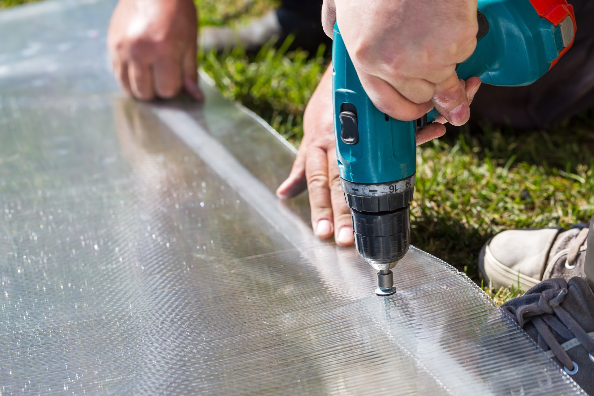 Worker drilling polycarbonate plastic